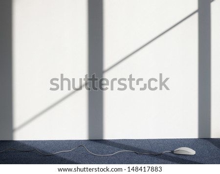 Closeup of a Computer mouse on carpeted floor against white wall