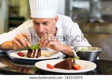 Closeup of a concentrated male pastry chef decorating dessert in the kitchen - stock photo