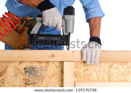 Closeup of a construction worker with a nail gun working on a wall he is building. - stock photo