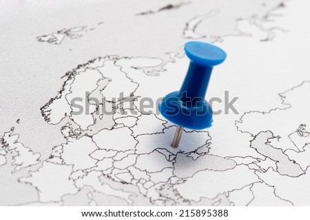 Closeup of a contour map of Europe with a blue pin on Ukraine. - stock photo