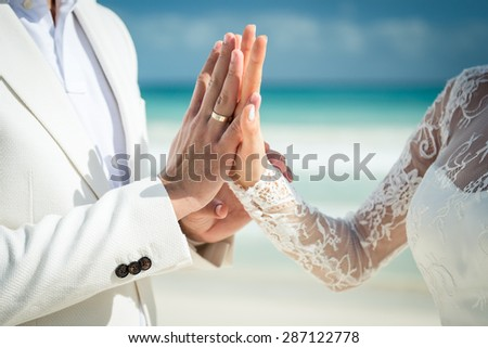 Closeup of a couple exchanging wedding rings during a wedding ceremony on the beach. Destination wedding. - stock photo