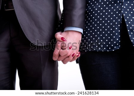 Closeup of a couple holding hands isolated in white - stock photo