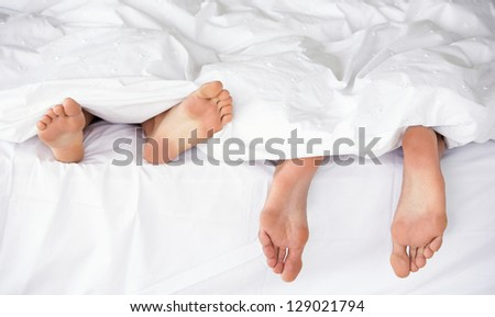 stock-photo-closeup-of-a-couple-s-feet-in-bed-sleeping-129021794.jpg