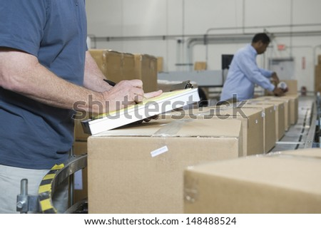 Closeup of a cropped man writing with worker in background at distribution warehouse - stock photo