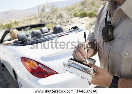 Closeup of a cropped police officer writing traffic ticket to woman sitting in car - stock photo