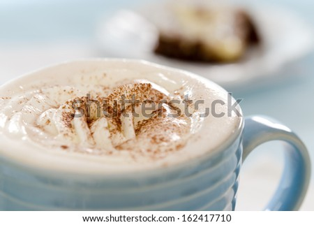 Closeup of a cup of hot chocolate with whipped cream.
