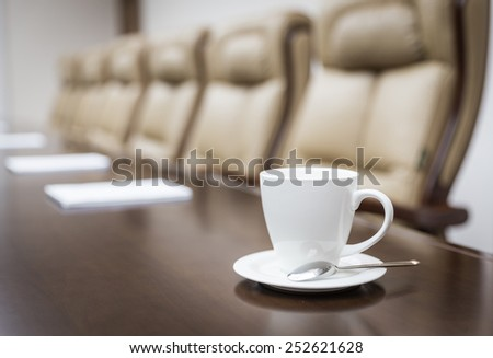 Closeup of a cup on table in empty corporate conference room before business meeting in office