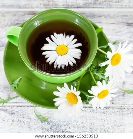 Closeup of a cup with herbal chamomile tea served in green ceramic cup and few wild flowers on white painted wooden surface. Square crop - stock photo