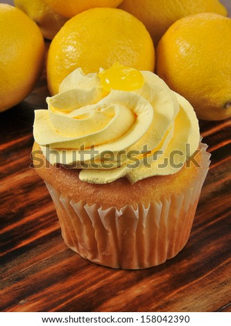 Closeup of a cupcake with lemon frosting and fresh lemons - stock photo