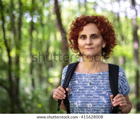 Closeup of a curly redhead woman with backpack outdoor in the forest - stock photo