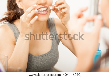 Closeup of a cute brunette applying a whitening strip on her teeth in front of a mirror in the bathroom - stock photo