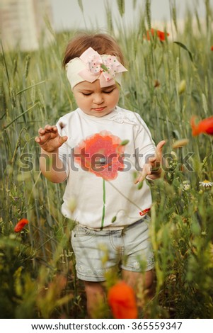 Closeup of a cute girl in poppy field of flowers in the open air. The girl in the poppies. Happy kid with poppies.