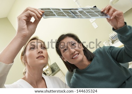 Closeup of a dentist and patient examining x-ray in the dental clinic - stock photo