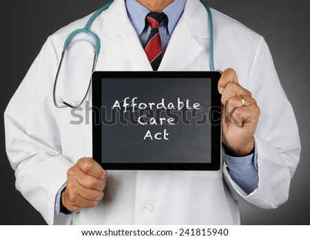 Closeup of a doctor holding a tablet computer with a chalkboard screen with the words Affordable Care Act (Obamacare). Man is unrecognizable.  - stock photo