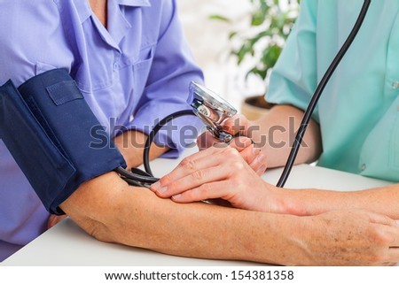 Closeup of a doctor taking patient's pulse - stock photo