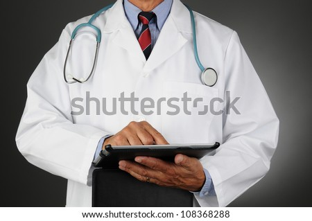 Closeup of a doctor using a tablet computer.  Horizontal format over a light to dark gray background. Man is unrecognizable. - stock photo