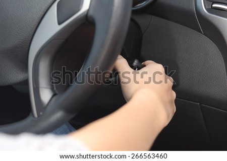 Closeup of a driver hand starting the car with the key - stock photo