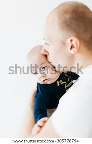 Closeup of a father kissing his baby boy looking down - isolated on white.
