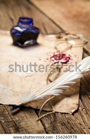 Closeup of a feather lying on old sheet of paper - stock photo