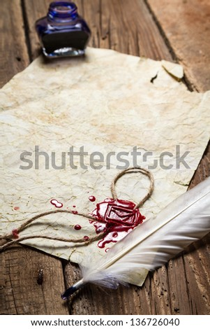 Closeup of a feather lying on vintage letter with red sealing wax - stock photo