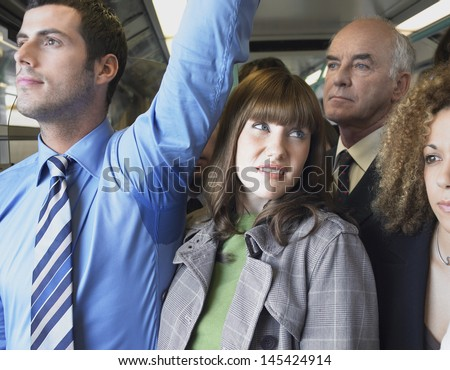 Closeup of a female commuter standing by man's wet armpit in a crowded train - stock photo