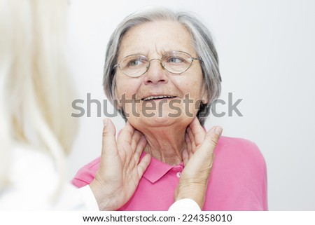 Closeup of a female doctor examining her senior  patient. - stock photo