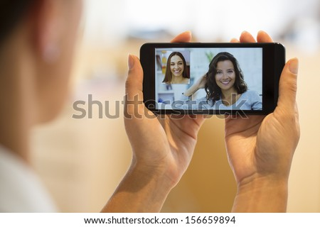 Closeup of a female hand holding a cell phone during a skype video call with her friend  - stock photo