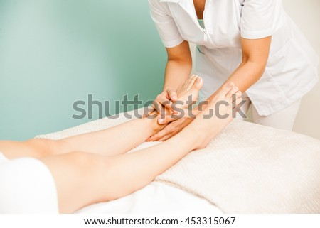 Closeup of a female masseuse giving a foot massage to one or her clients at a health and beauty spa
