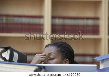 Closeup of a female office worker with laptop behind stacks of documents in office - stock photo