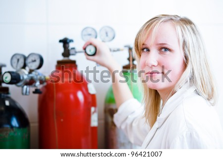Closeup of a female researcher/chemistry student carrying out experiments in a lab (color toned image) - stock photo
