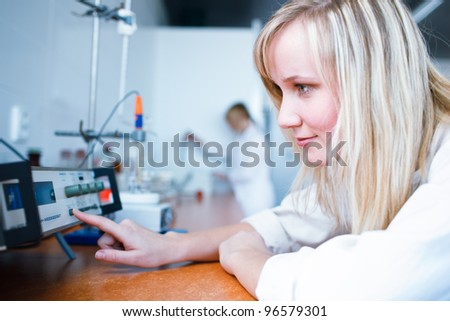 Closeup of a female researcher/chemistry student carrying out experiments in a lab, measuring PH (color toned image) - stock photo