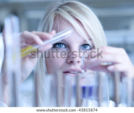 Closeup of a female researcher holding up a test tube and a retort and carrying out experiments (color toned image)