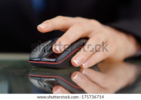 Closeup of a female's hand working on black computer mouse. - stock photo
