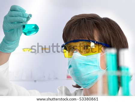 Closeup of a female scientist examining the green liquid contents of a conical flask in the lab - stock photo