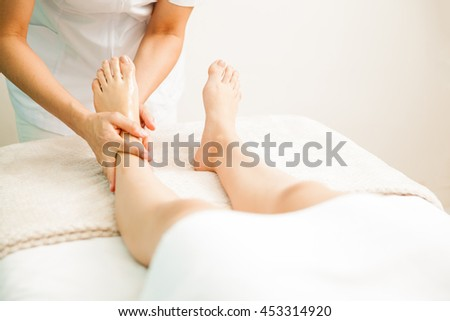 Closeup of a female therapist giving a foot massage to a client at a health and beauty spa