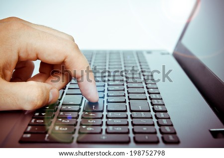 closeup of a finger pressing laptop keyboard