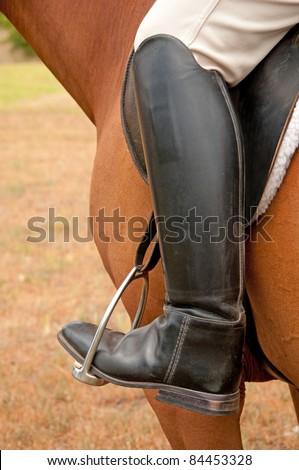 Closeup of a foot in a stirrup - stock photo