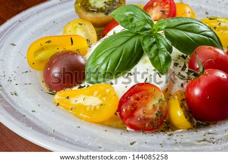 closeup of a fresh heirloom tomato and buffalo mozzarella salad garnished with fresh green basil served on a wooden table - stock photo