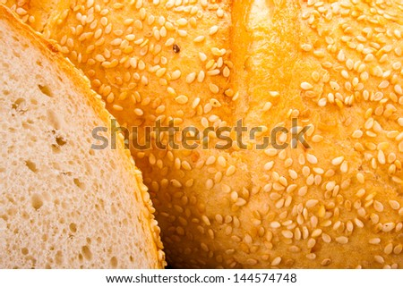 Closeup of a fresh piece of fresh bread with sesame seeds, with a cut slice - stock photo