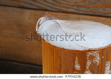 Closeup of a full pitcher of cold beer in front of a rustic wood background. - stock photo