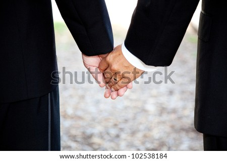Closeup of a gay couple holding hands, wearing a wedding ring.  Couple is a hispanic man and a caucasian man. - stock photo