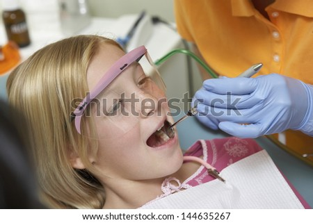 Closeup of a girl having her teeth examined at the dental clinic