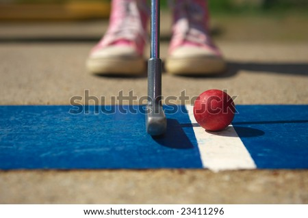Closeup of a girl in pink trainers getting ready to putt.
