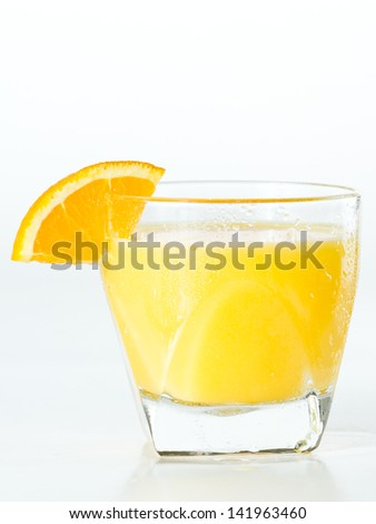 closeup of a glass filled with fresh orange juice garnished with an orange slice isolated on a white background - stock photo