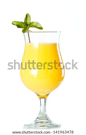 closeup of a glass filled with fresh orange juice garnished with fresh mint isolated on a white background - stock photo