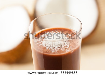 Closeup of a glass of coconut and chocolate smoothie, topped with ground coconut. - stock photo
