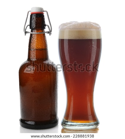 Closeup of a glass of dark beer with a frothy head next to a swing top brown beer bottle. Straight on shot on a white background with reflection. Both items are cover with water drops. - stock photo
