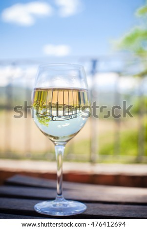Closeup of a glass of white wine with the background of Tuscany hills