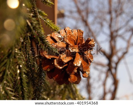 Closeup of a glittered pinecone on a green pine bough garland decorating a shop front or home at Christmas.   - stock photo