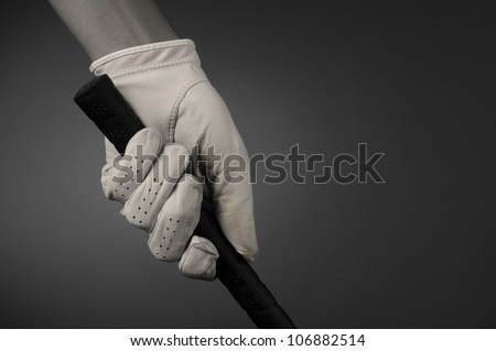 Closeup of a golfers hand on the handle of a golf club. Horizontal format on a light ot dark background. Slight sepia toning for an old fashioned look. - stock photo